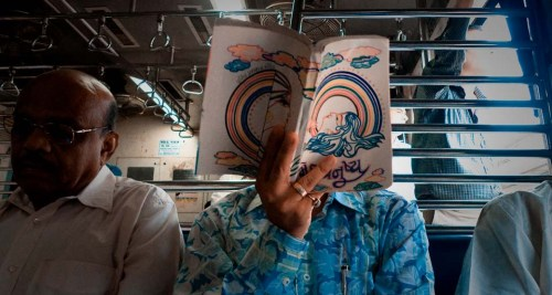 Man reading book: Western Railway Local Train at Vile Parle, Mumbai. Photo : Gopal MS