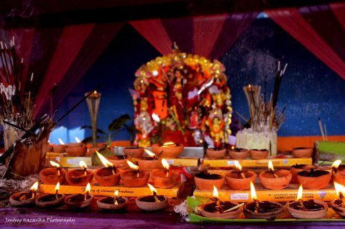 Earthen lamps being lit at a Puja pandal