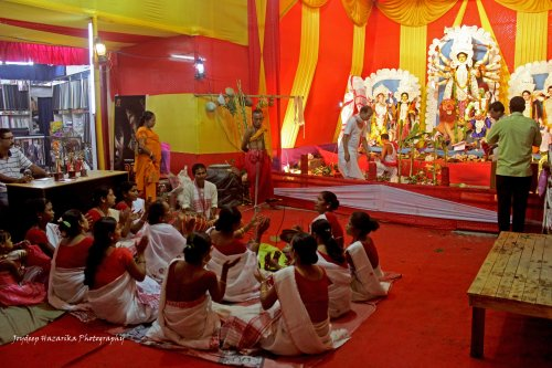 A group of women performing traditional kirtan - Aai Naam at a puja pandal